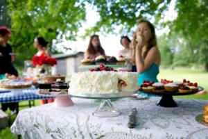 Girl eats cake at a garden party